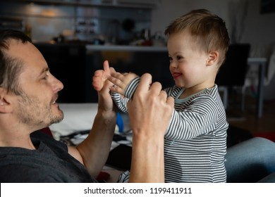 Cute boy with Down syndrome playing with dad on in home living room