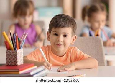 Cute boy drawing in classroom