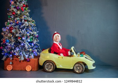 Cute boy dressed in festive costume of Santa Claus is carrying Christmas tree decorating Xmas tree with balls and garlands on yellow car. boy plays and waits for gifts. Christmas Eve
