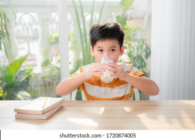Cute boy drinking glass of milk sitting at a table after doing the homework
