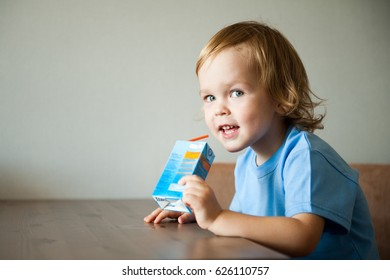 Cute boy drinking juice or milk from a packet.