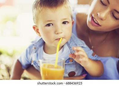 Cute boy drinking orange juice