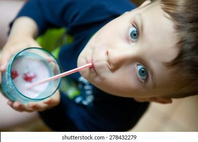 Cute boy drinking smoothie