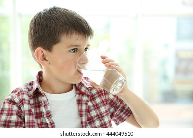 Cute boy drinking water on kitchen