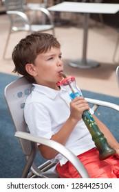 Cute boy drinks refreshing drink in summer in cafe. colorful granita
