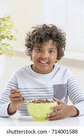 Cute boy eating cereals for breakfast on kitchen background