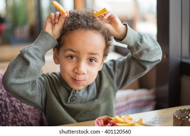 Cute boy eating french fries in restaurant - Funny faces