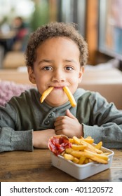 Cute boy eating french fries in restaurant - Funny joke