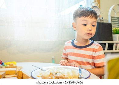 Cute boy eating rice and fried pork with garlic and listen fairy tales and stories. Copy space.