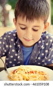 Cute boy eating spaghetti in cafe