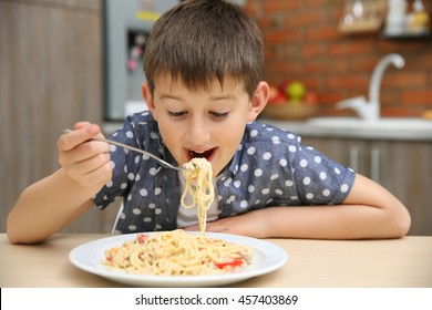 Cute boy eating spaghetti on kitchen