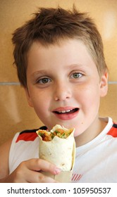 The cute boy eating wrap sandwich