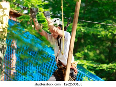 Cute boy enjoying activity in climbing adventure park on summer sunny day. Kid climbing in rope playground structure. Safe Climbing extreme sport with helmet insurance. Child in forest adventure park