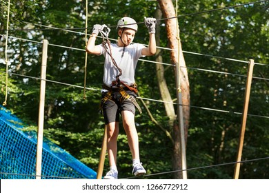 Cute boy enjoying activity in climbing adventure park at sunny summer day. Kid climbing in rope playground structure. Safe climbing with helmet insurance. Child in forest adventure park, extreme sport