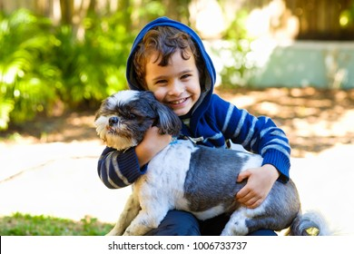 Cute boy enjoying the outdoors in a home yard setting with his dog.