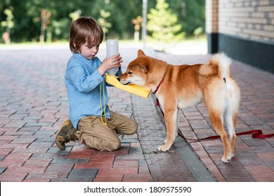 Cute boy feeds his dog from a portable plastic bottle. Thirsty dog. Travel water bottle. Portable Pet Water Bottle concept