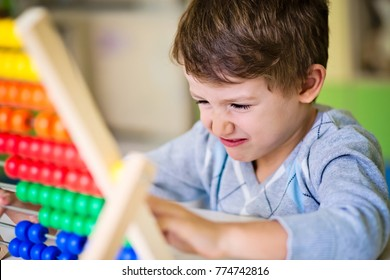 Cute boy feeling bored and frustrated while playing with abacus at kindergarten. Hyperactive kid having difficulties counting.