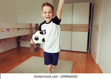 A cute boy in football suit and with ball looks forward to world cup