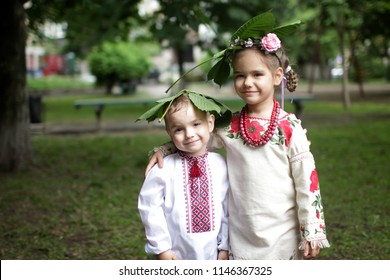 Cute boy and girl, brother and sister, in traditional embroidered clothes covering with horse-chestnut leaf, a symbol of Kyiv city, during the rain, Ukrainian history and culture, outdoor portrait