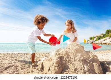 Cute boy and girl building sandcastle on the beach