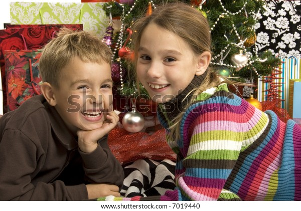 a cute boy and girl in front of the christmas tree with gifts