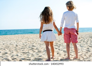 Cute boy and girl holding hands looking at sea.