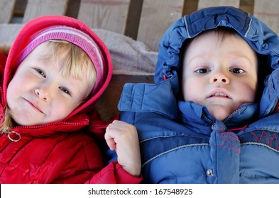 Cute boy and girl lying down looking up at the camera in winter jackets.