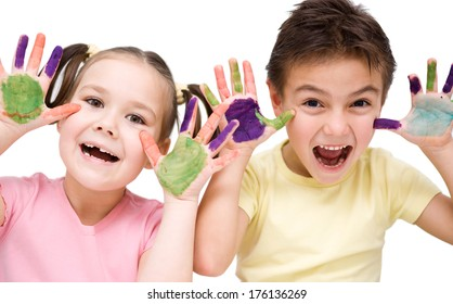 Cute boy and girl showing her hands painted in bright colors, isolated over white