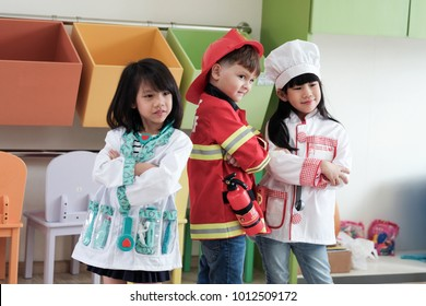 Cute boy and girls playing as fireman, doctor and cook occupation in kindergarten class, kid occupation, education concept