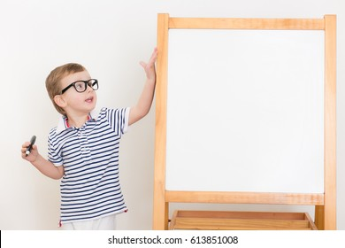 Cute  boy with glasses like a student  drawing empty desk