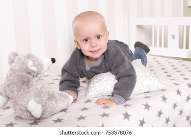 A cute boy in a gray sweatshirt on a crib in the children's room.