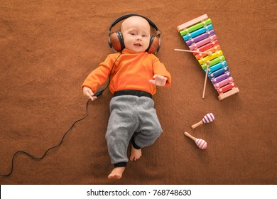 Cute boy with headphones and xylophone on color textile
