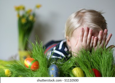 Cute boy hiding in studio behind grass with easter eggs