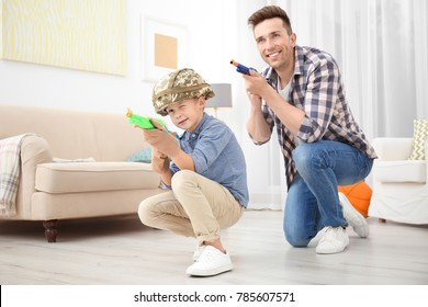 Cute boy and his father playing with toy guns at home