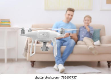 Cute boy and his father playing with drone at home