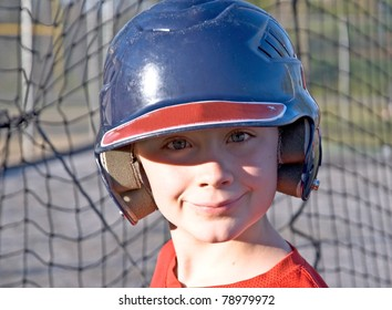A cute boy with his helmet on waiting for his turn at batting practice.