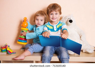 Cute boy and his little sister  reading a book together  at home