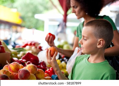 Cute boy with his mother buying fresh vegetables at the farmer's market