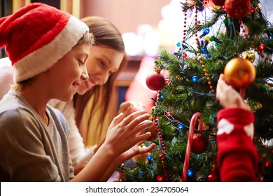 Cute boy and his mother decorating Christmas tree for holiday