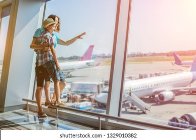 Cute boy with his mother looking at planes in the airport