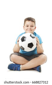 Cute boy is holding a football ball made of genuine leather. Sitting on floor.  Isolated on a white background. Soccer ball