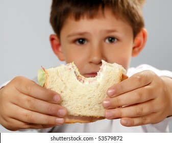 cute boy holding his sandwich . Selective focus on hands and sandwich