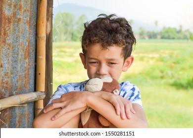 a cute boy holding the monkey doll with sad face. sad boy