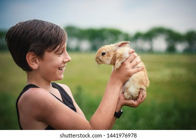 Cute boy holding a rabbit