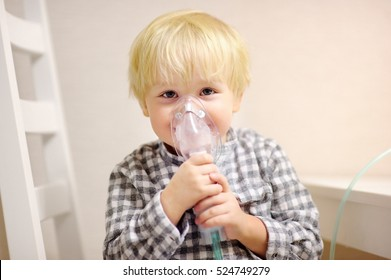 Cute boy inhalation therapy by the mask of inhaler. Close up image of a little kid with respiratory problem or asthma. Sick boy with clear oxygen mask.