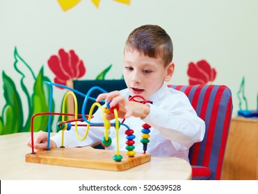 cute boy, kid in wheelchair solving logical puzzle in rehabilitation center for children with special needs
