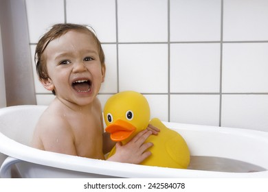Cute boy laughing in bathtub with rubber duck