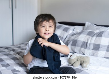 Cute boy learning how to put cloth on, 4 year old kid sitting in bed with teddy bear  wearing school jumper,boy getting dressed and get ready for school, Child dressing uniform in bed room.