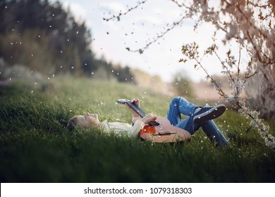 Cute boy lies on the grass with a guitar on sunset.