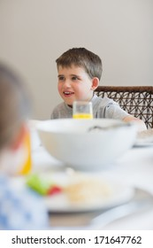 Cute boy looking away at breakfast table
